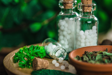 Homeopathic globules in small bottles with mint leaves, homeopathy concept