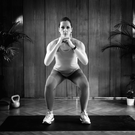 Woman Doing Squats on High-intensity interval training at home. Archivio Fotografico