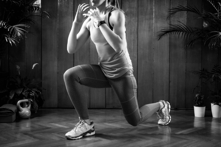 Woman doing lunges on High-intensity interval training at home Фото со стока