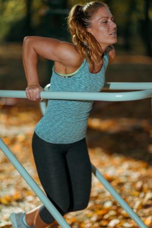 Vrouw trainen op parallelle staven buiten in de herfst, in openbaar park