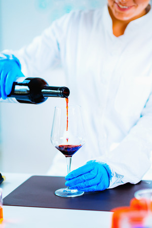 Quality control expert inspecting red wine in the laboratory