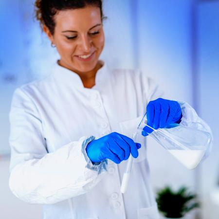 Experto en control de calidad inspeccionando la leche en el laboratorio Foto de archivo