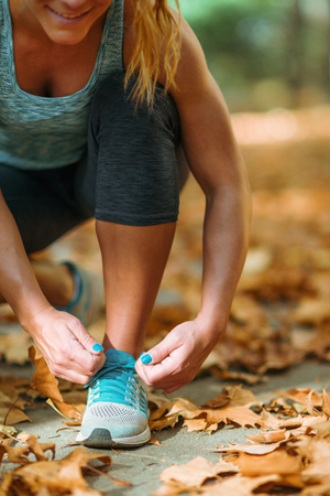 Woman Exercising Outdoors in The Fall. Kneeling and tying shoe.