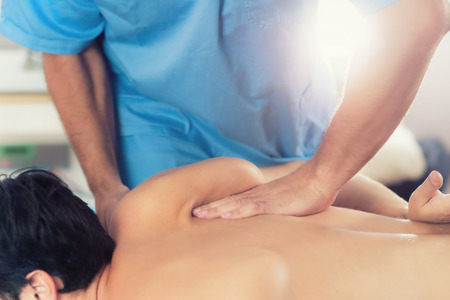 Physiotherapist doing healing treatment on mans back. Therapist wearing blue uniform. Osteopathy. Chiropractic adjustment, patient lying on massage table