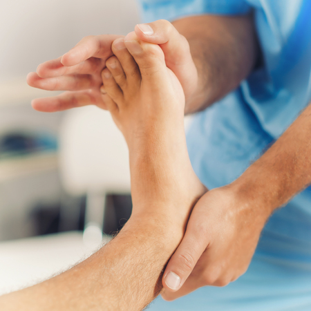 Physiotherapist doing healing treatment on patient foot. Therapist wearing blue uniform. Osteopathy, Chiropractic foot adjustment