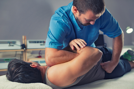 Physiotherapist doing healing treatment on man's back. Therapist wearing blue uniform. Osteopathy. Chiropractic adjustment, patient lying on massage table