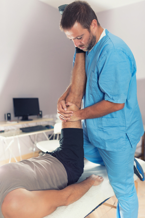 Physiotherapist doing healing treatment on patient leg. Therapist wearing blue uniform. Osteopathy. Chiropractic adjustment, patient lying on massage table