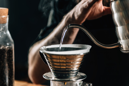 Close up of a young male barista pouring boiling water into Kalita Wave Dripper to brew coffee and measure it on digital scale in coffee shop. Banco de Imagens - 108303975