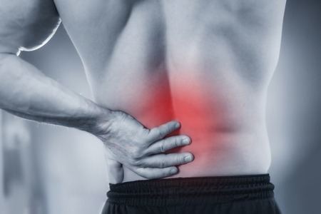 Close up image of male holding painful lower back.