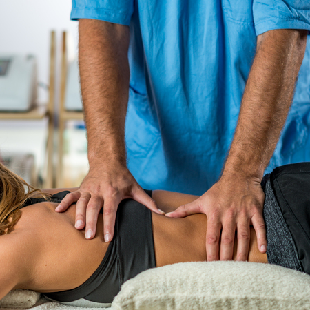 Physical therapy. Therapist applying strong pressure onto lower back muscles Stock Photo