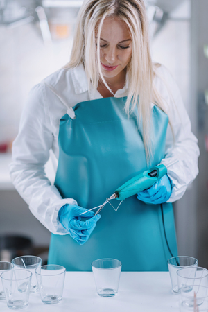 Beautiful blond hairyoung woman holding hot glue gun for gluing cotton wick on the bottom of the glass. Candle making process. Wearing protective work wear.