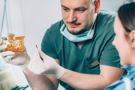 Dentista explicando el procedimiento de implante dental al paciente en la clínica Foto de archivo