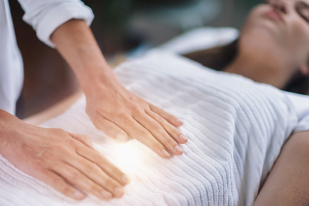 Female therapist performing Reiki therapy treatment holding hands over womans stomach. Alternative therapy concept of stress reduction and relaxation.