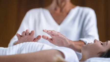 Professionele Reiki-genezer die Reiki-behandeling doet aan jonge vrouw in kuuroordcentrum. Healing en balanceren van hart- en kruinchakra's.