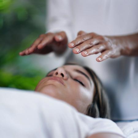Imagen cuadrada del terapeuta de Reiki tomados de la mano por encima de la cabeza del paciente y transfiriendo energía. Adolescente pacífica acostada con los ojos cerrados.