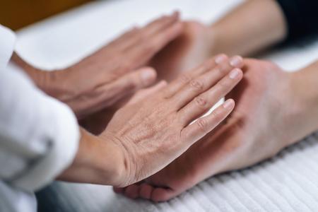 Manos del terapeuta de Reiki curando y equilibrando los chakras de los pies. Concepto de sanación energética