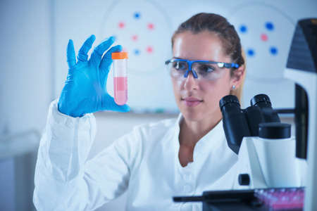 Young female scientist holding liquid sample Foto de archivo