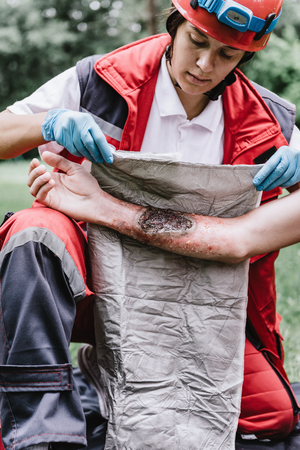 First aid paramedic in training, treating third degree burns Фото со стока