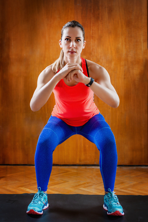 Woman Doing Squats on High-intensity interval training at home.