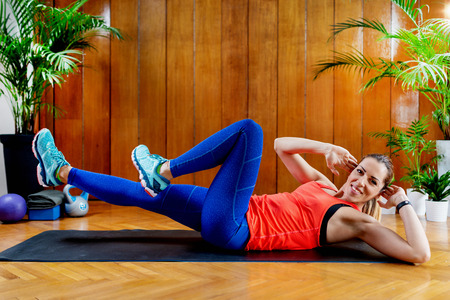 Woman doing Crunches on High-intensity interval training at home