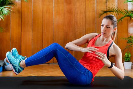 Femme entraînant des abdominaux sur un entraînement par intervalles à haute intensité à la maison