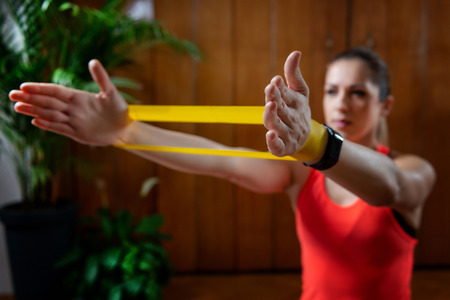 Woman exercising with rubber resistance band at home 版權商用圖片