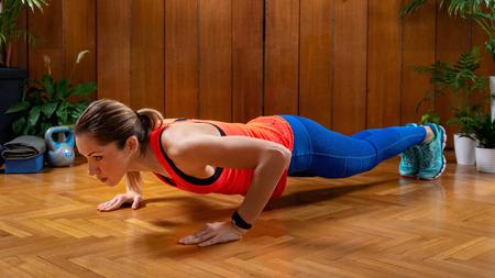 Femme faisant un entraînement par intervalles à haute intensité à la maison. Femme faisant des pompes