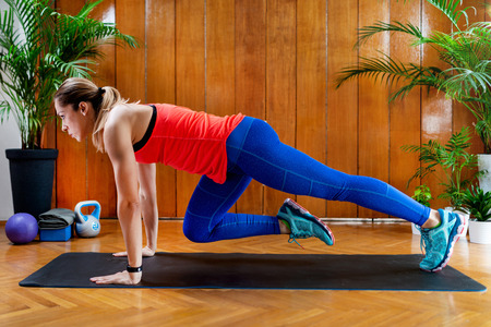 Woman doing mountain climbers on High-intensity interval training at home
