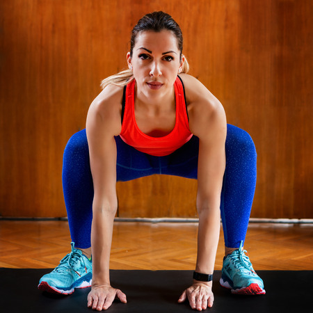 Woman Doing Sumo Squats on High-intensity interval training at home.