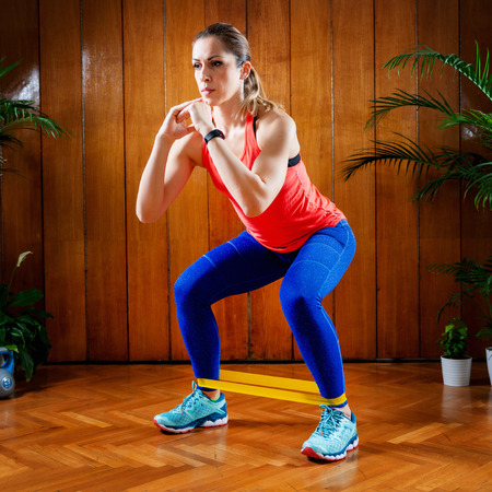 Woman exercising legs with rubber resistance band at home