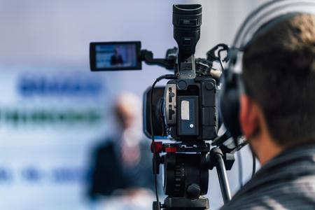 Cameraman che indossa le cuffie e registra un altoparlante maschio in piedi sul palco durante l'evento mediatico della conferenza stampa. Archivio Fotografico