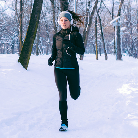 Female athlete exercising in park on winter day in park