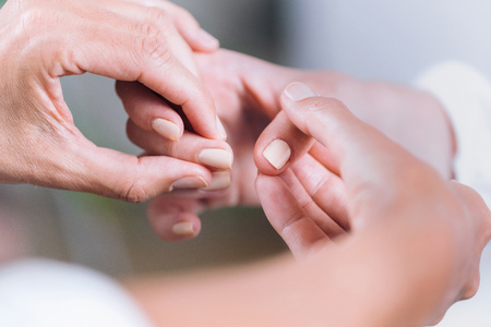 Close up horizontal image of female hands performing muscle testing at Theta healing session. Therapist and patient sitting and wearing white clothes. Energy healing concept Stockfoto