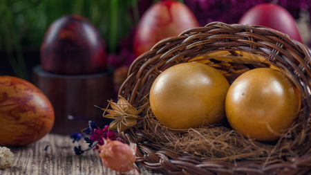 Close up image of two beautiful golden Easter eggs in wicker basket. Green grain grass decoration in background. Easter holiday concept. 版權商用圖片 - 114915394