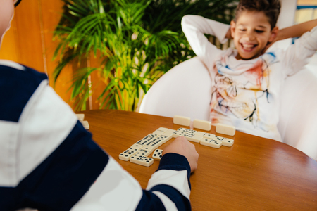 Boy playing dominoes at home.