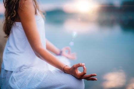 Piękna młoda kobieta robi ćwiczenia jogi nad jeziorem. Siedząc w pozycji lotosu