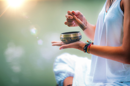 Close up image of woman's hands holding Tibetan bowl by the Water 스톡 콘텐츠 - 115177710