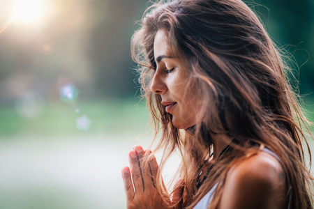 Young woman meditates, practicing yoga in nature. Hands in prayer position. Stock Photo