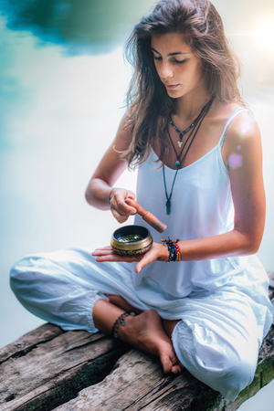 Close up image of woman's hands holding Tibetan Singing Bowl Outdoors