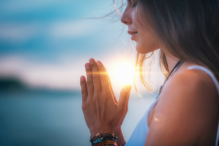Young woman meditating with her eyes closed, practicing Yoga with hands in prayer position. Stockfoto