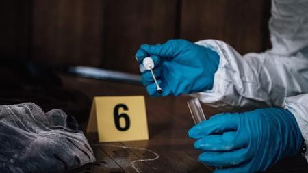 Enquêteur judiciaire recueillant des preuves de sang sur une scène de crime