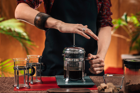 Barista Making French Press Coffee. Close up image of hands female barista making French press coffee Standard-Bild
