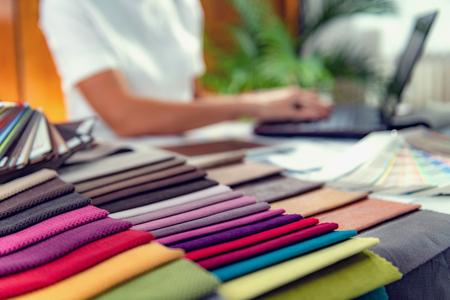 Diseñador de interiores femenino elegir muestras de materiales de muebles en un estudio.