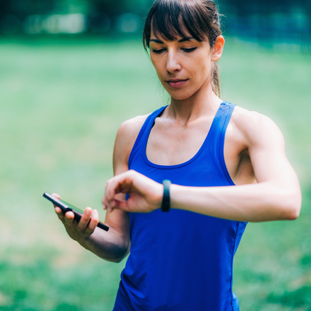 Woman checking progress on smart watch after outdoor training Stock Photo