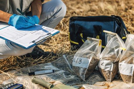 Prueba de suelo. Ingeniero agrónomo tomando notas en el campo. Protección del medio ambiente, certificación de suelos orgánicos, investigación.