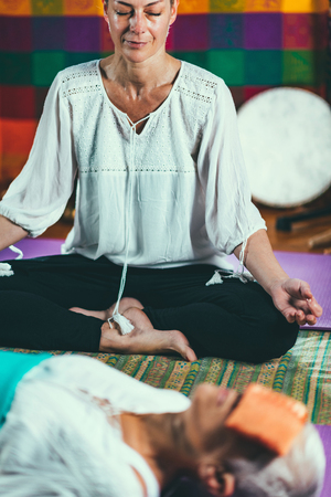 Guided meditation. Senior woman and mid adult woman lying on the floor and meditating