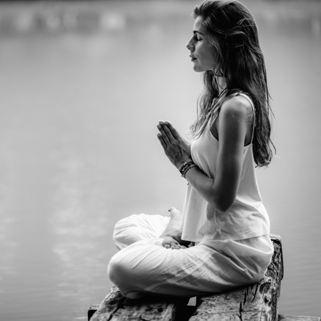 Young woman meditates, practicing yoga in nature. Sitting in lotus pose with hands in prayer position.