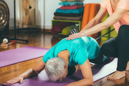 Yoga guru with senior woman, doing yoga Imagens