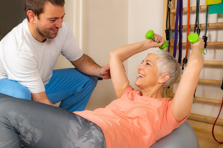Senior woman exercising on Pilates ball with coach's help
