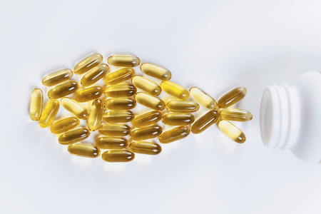 Omega 3 supplements.  Softgel supplement capsules, fish shape 免版税图像